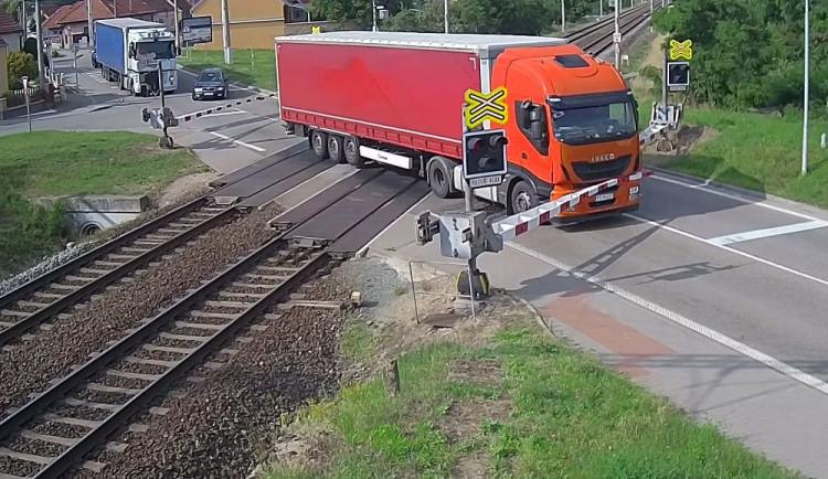 VIDEO: Řidič kamionu ignoroval červenou na přejezdu, kvůli vlaku pak prorazil závory